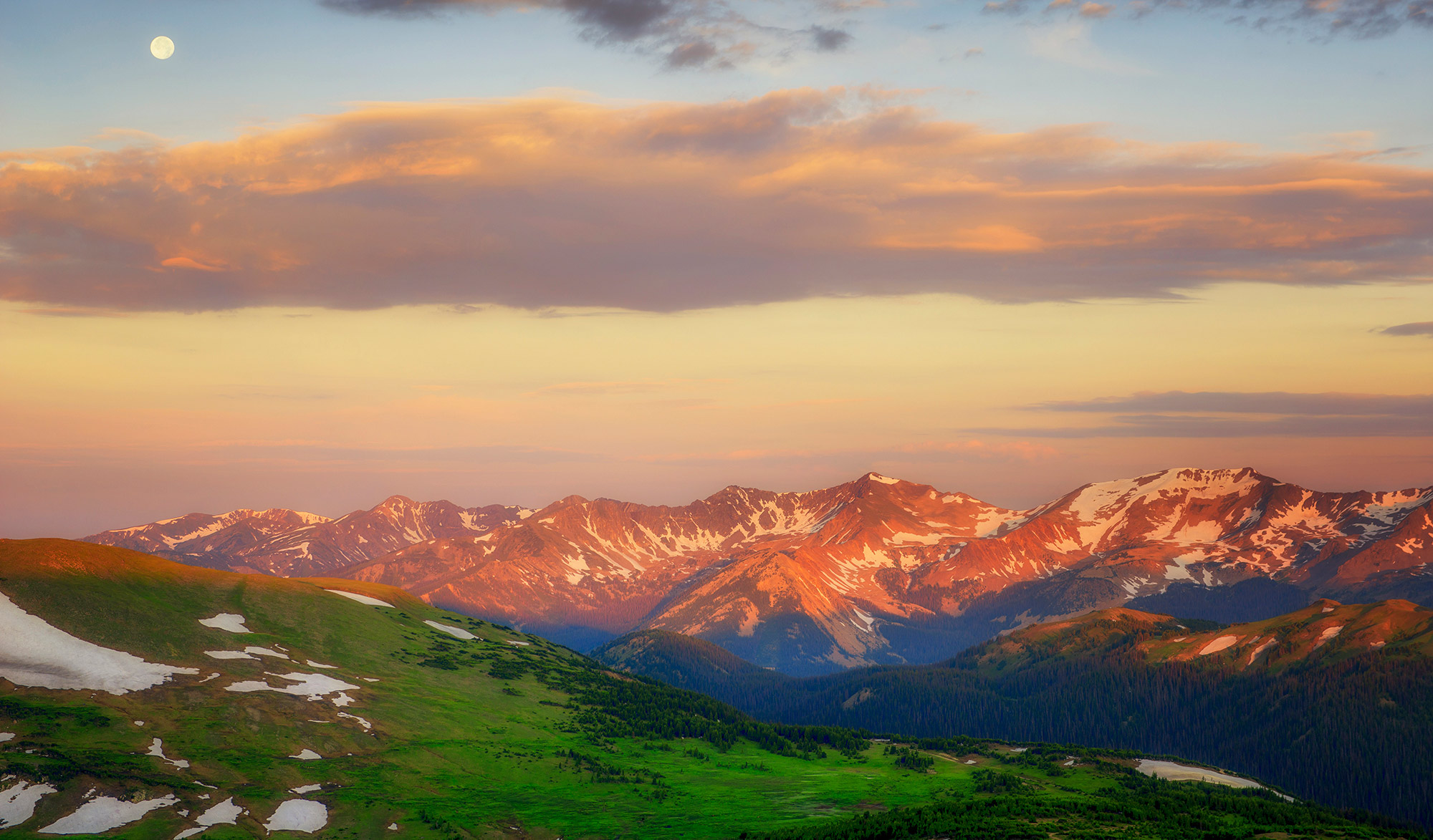 The full moon sets over the Never Summer Mountains amid dawan's summer glow  from the top of Trail Ridge Road near the Alpine Visitors Center in Rocky Mountain National Park, Colorado.